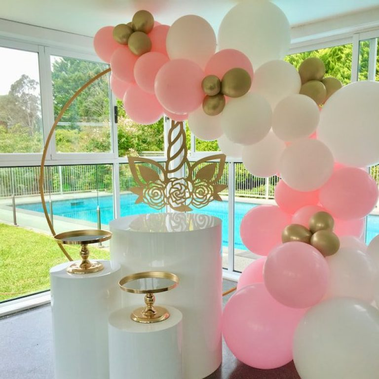 A pink and white balloon garland drapes over a gold hoop backdrop, with white plinths and gold cake stands