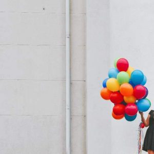 Person Holding Bunch of Balloons