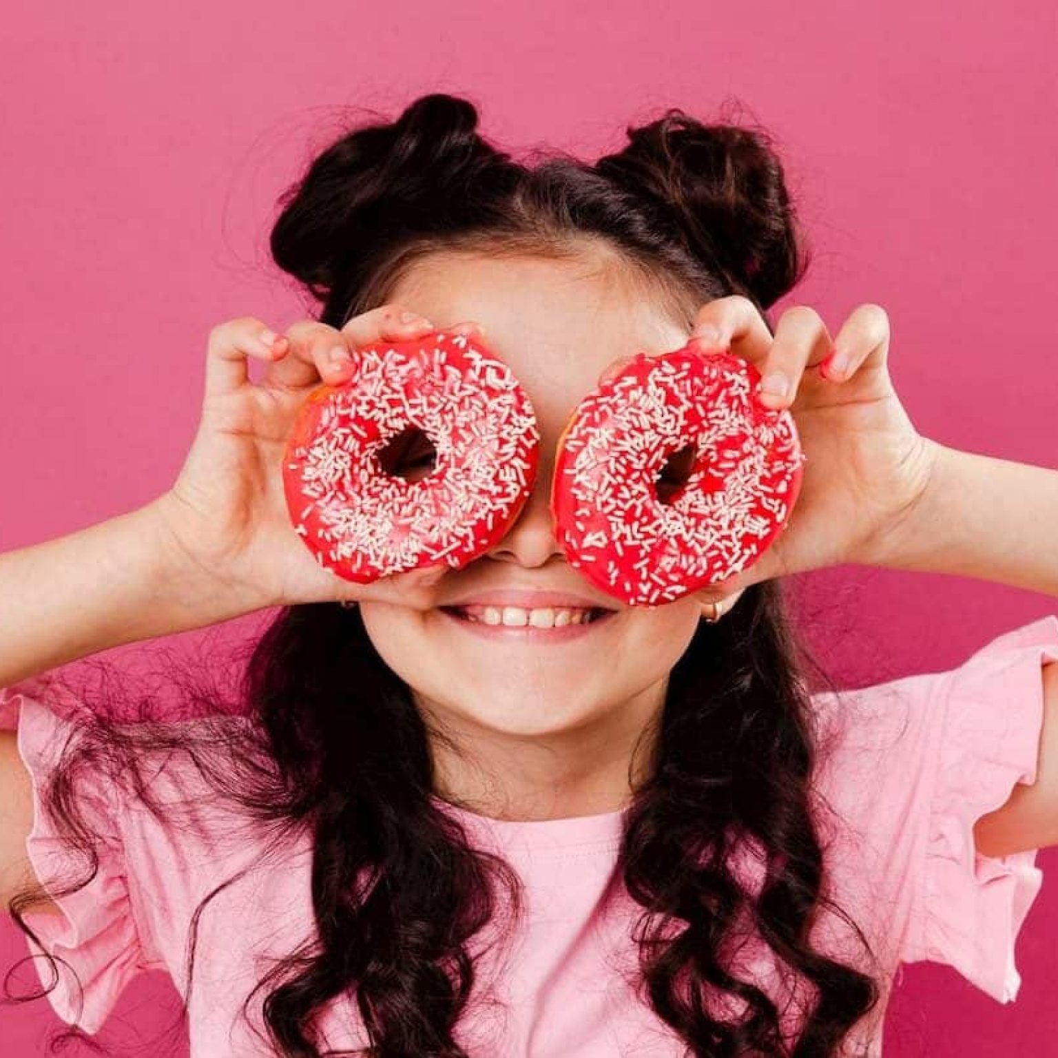 Child holding pink donuts over eyes, showing healthy party food