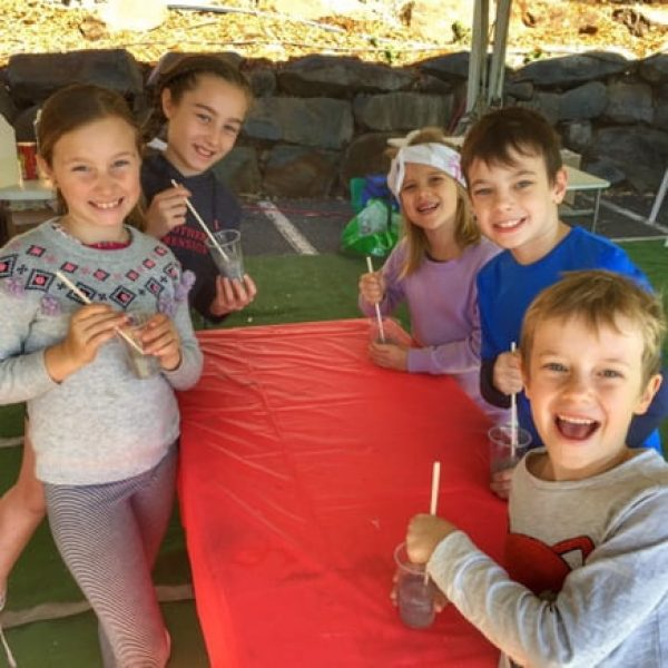 Children at a Slime party smiling while they make slime. Kids science party!