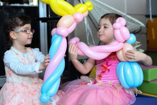 Children showing each other their princess balloons