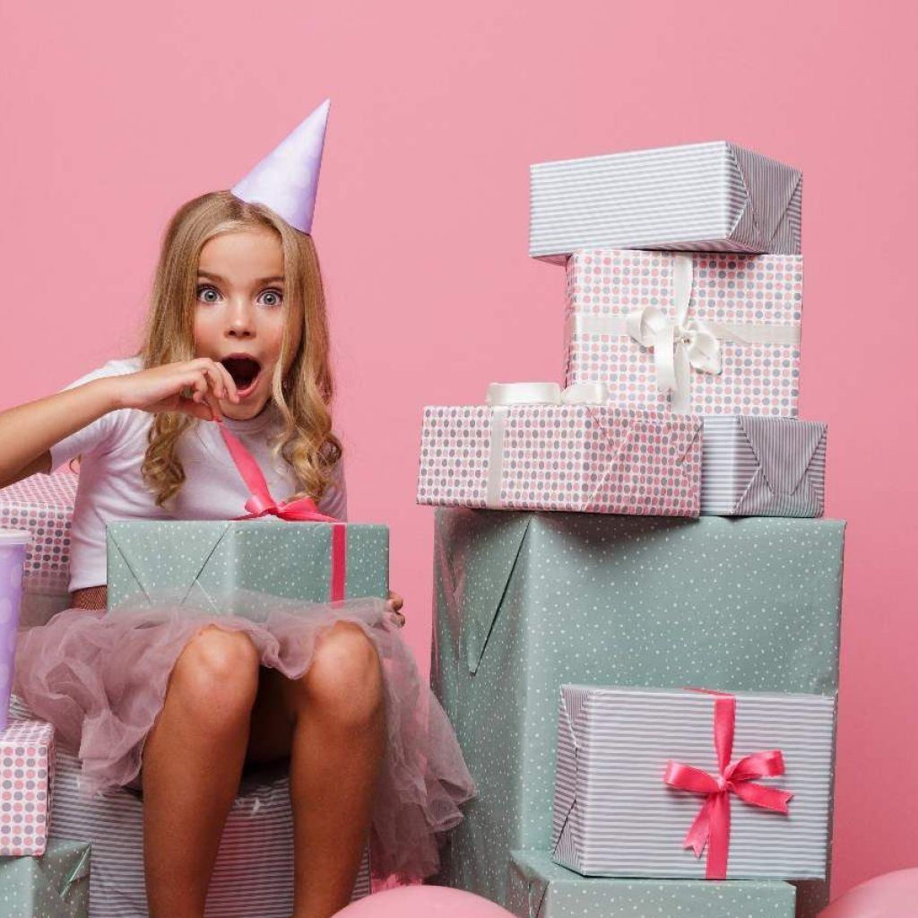 Girl Opening Presents with Balloons Around