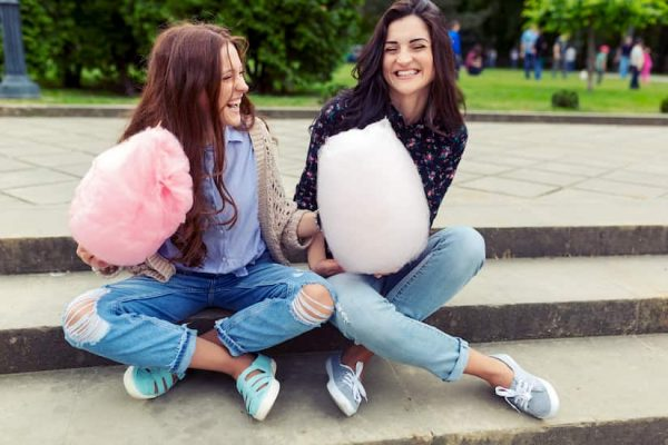 Teenagers laughing while holding fairy floss