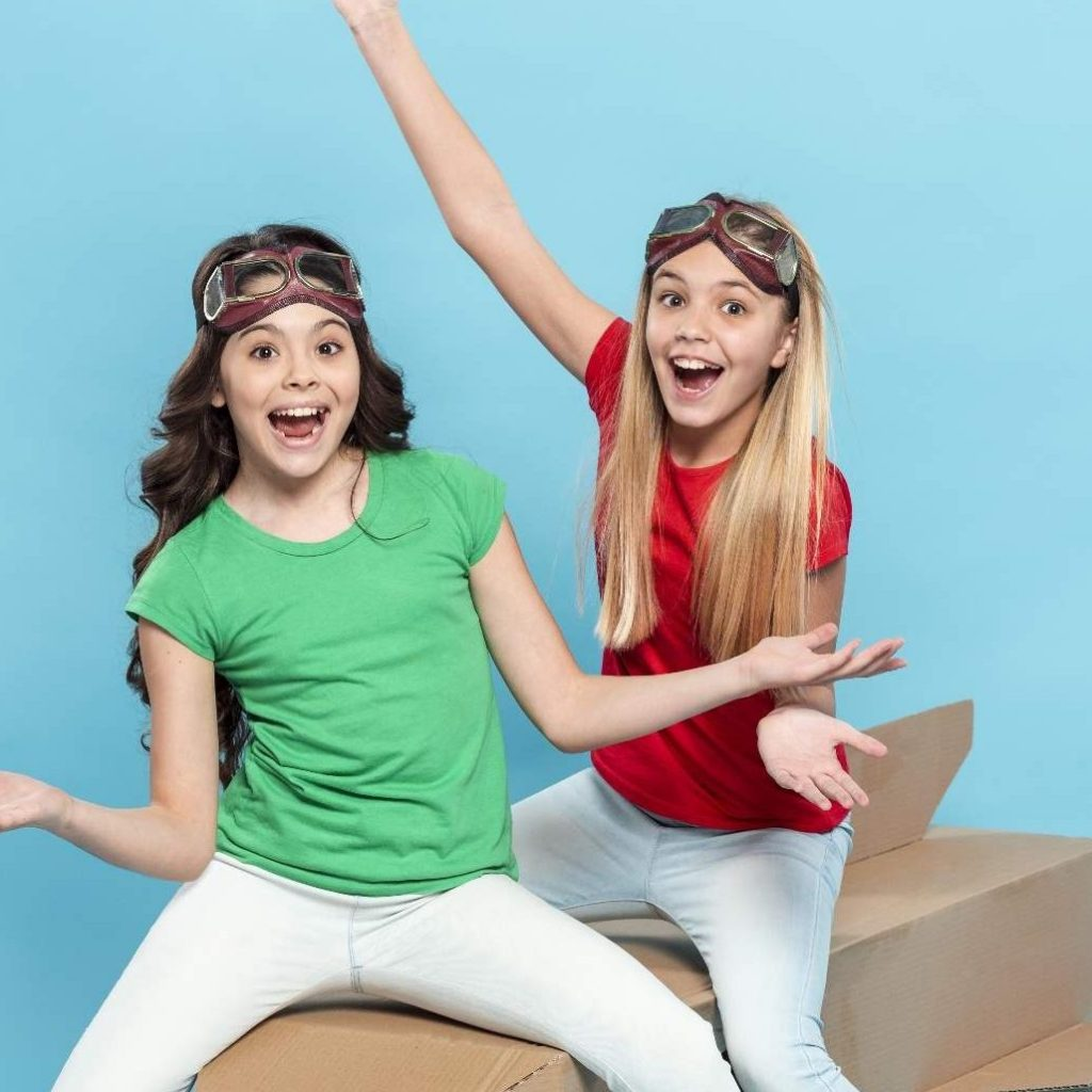 Girls in Rainbow Clothes Sitting on Boxes on Blue Background