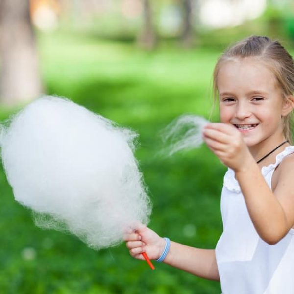 Girl eating fairy floss in park from a fairy floss machine hire Melbourne