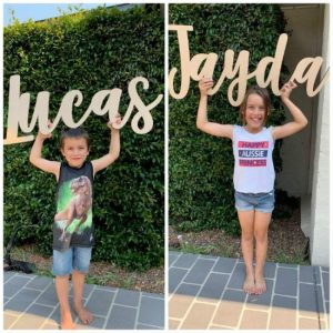 Kids Holding Wooden Lasercut Signs Saying Lucas and Jayda