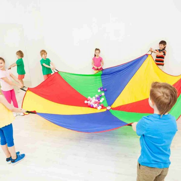 Kids playing with a rainbow parachute
