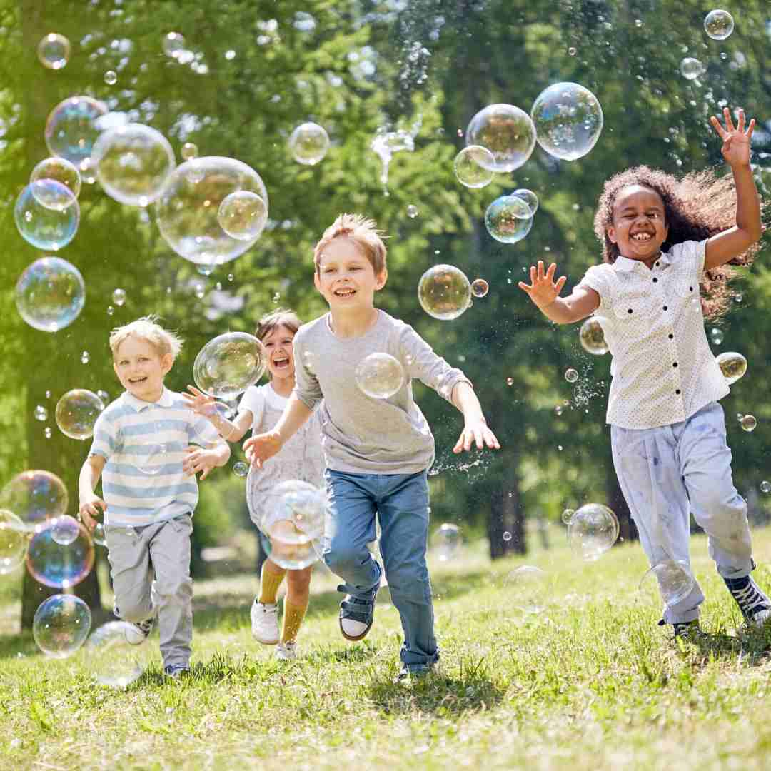 Kids catching bubbles in park