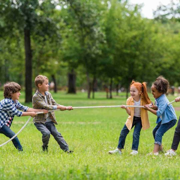 Kids playing tug of war in a park