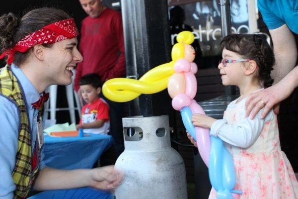 Child receiving a balloon design from a balloon twister