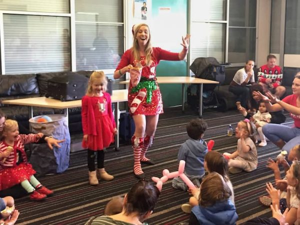 Christmas elf waving fingers in air to perform a magic trick