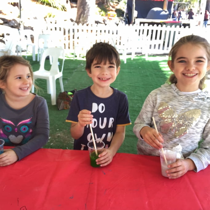 Children at a slime party stirring their slime