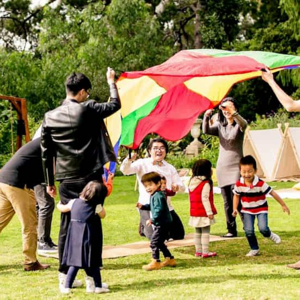 kids playing with rainbow parachute