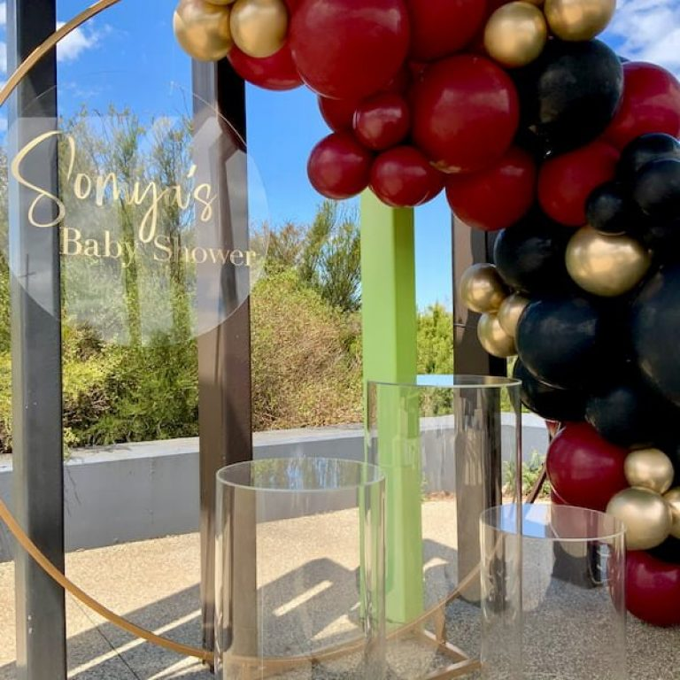 Red, black and gold balloon garland drapes over a hold backdrop with clear plinths