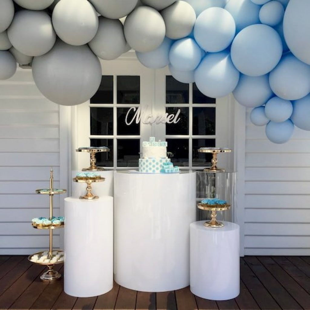 White plinths with gold cake stands and a balloon garland over hanging