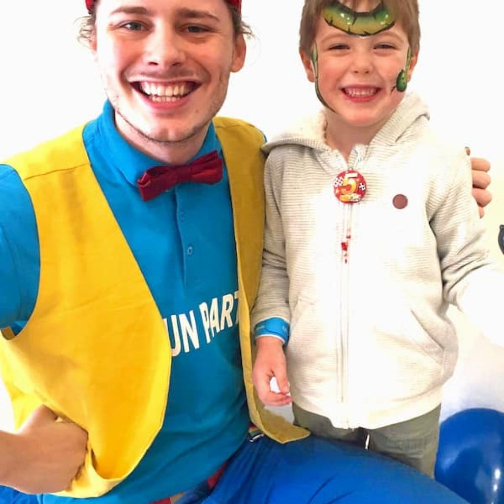 Children's party entertainer smiling with a birthday child.